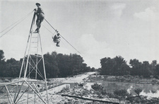 Waesta cableway for measuring the water velocity at different flood heights; gauging the Omuramba Omatako on Farm Ousema, February, 1962. In the chair is Mr. H. W. Stengel. On the tower Mr. W. F. W. Holch who constructed the apparatus. Photograph Dr. O. Wipplinger.